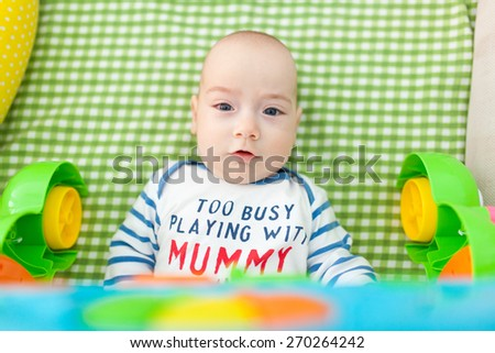 Portrait of an adorable child lying in bed looking at photographer. - stock photo