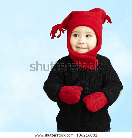 portrait of an adorable kid smiling wearing winter clothes against a blue background - stock photo