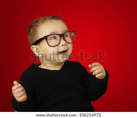portrait of an adorable kid wearing glasses and gesturing over a red background - stock photo
