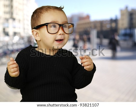 portrait of an adorable kid wearing vintage glasses at a crowded street - stock photo