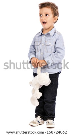 Portrait of an adorable little boy playing with his toy bear on white background - stock photo