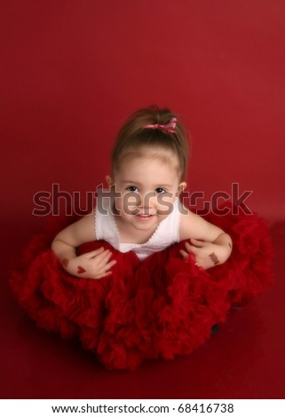 Portrait of an adorable little girl dressed in red on a red background for Valentines day or Christmas - stock photo