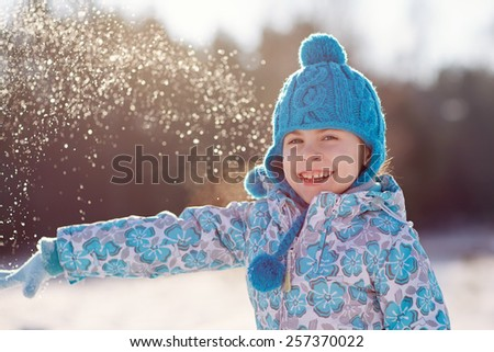 Portrait of an adorable little girl throwing a snowball on a sunny winter's day  - stock photo