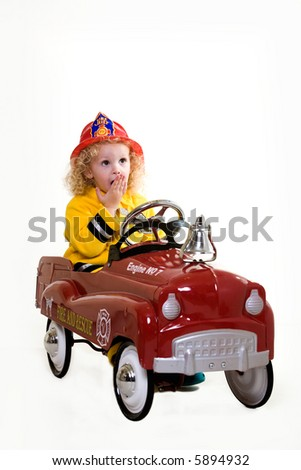 Portrait of an adorable little three year old boy wearing fireman costume sitting in a toy firetruck over white - stock photo