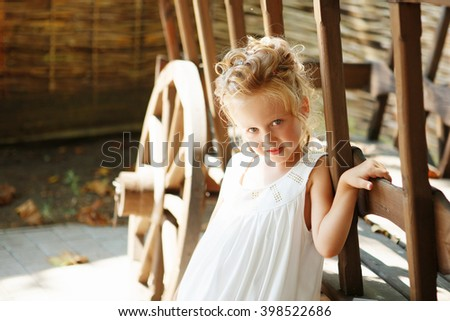 Portrait of an adorable preschool age girl with a hairdo with hairpins on her head. Positive emotions. Happy child. - stock photo