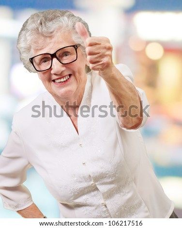 portrait of an adorable senior woman doing a good gesture against an abstract background - stock photo