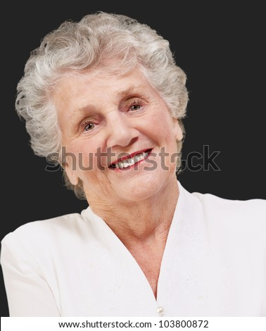 portrait of an adorable senior woman standing over a black background - stock photo