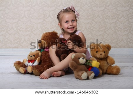 Portrait of an adorable toddler girl hugging a teddy bear on a vintage background