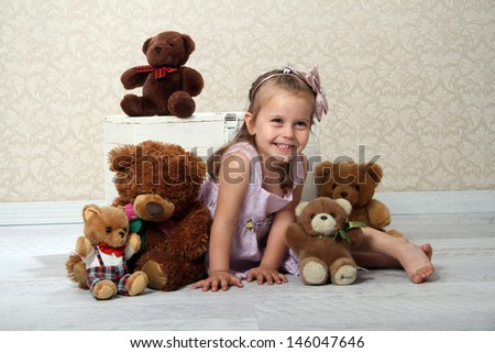 Portrait of an adorable toddler girl hugging a teddy bear on a vintage background - stock photo