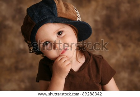 Portrait of an adorable toddler girl modeling a brown and blue jean denim hat posing for the camera - stock photo