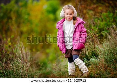 Portrait of an adorable toddler girl wearing fashion knitted clothes at autumn background