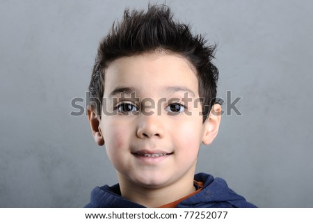 Portrait of an adorable young preschool boy with funny hair on dark background - stock photo