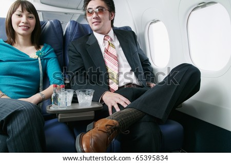 Portrait of an adult couple traveling in an airplane - stock photo