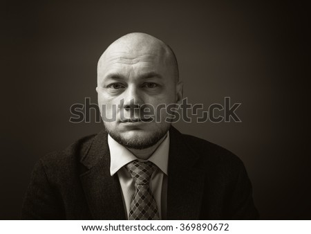 Portrait of an adult man in a business suit on a black background. Unhappy and thoughtful businessman. Sepia - stock photo