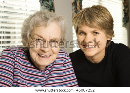 Portrait of an adult woman and senior woman smiling at the camera. Horizontal shot. - stock photo
