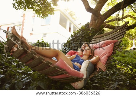 Portrait of an affectionate young couple lying on a hammock looking away smiling. Romantic young man and woman on garden hammock in backyard. - stock photo