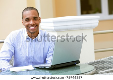 Portrait of an African American businessman with laptop outdoors - stock photo