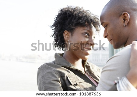 Portrait of an african american couple hugging and smiling by the river Thames in London city, UK.