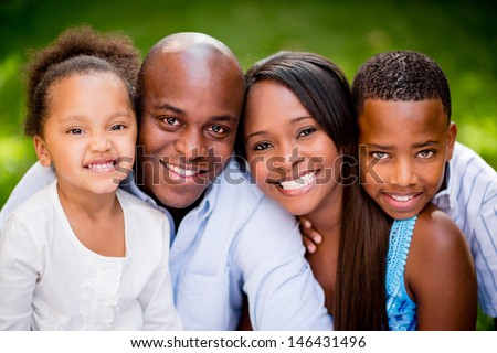 Portrait of an African American family looking very happy outdoors - stock photo