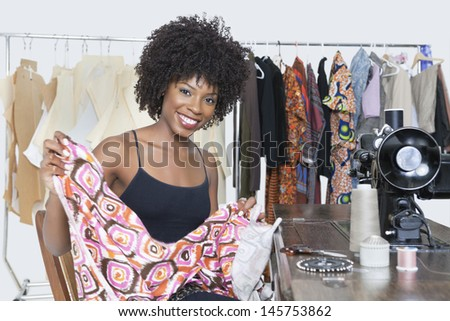 Portrait of an African American female fashion designer holding pattern cloth - stock photo