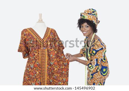 Portrait of an African American female fashion designer working on dashiki over gray background - stock photo