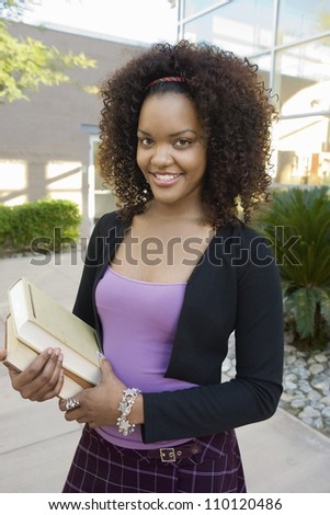 Portrait of an African American female holding books