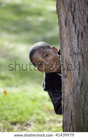 Portrait of an African American male child outdoors in Autumn being playful - stock photo