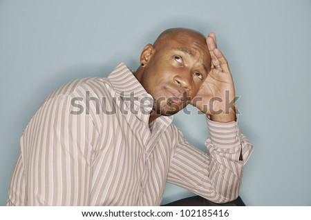Portrait of an African American man wiyh his head resting on his hand and eyes focused upward - stock photo