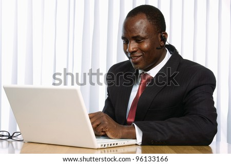 Portrait of an African American sitting on the desk with laptop