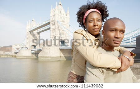 Portrait of an african american tourist couple visiting the Tower of London overlooking the river, being thoughtful. - stock photo