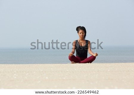 Portrait of an african woman sitting at beach in yoga pose  - stock photo
