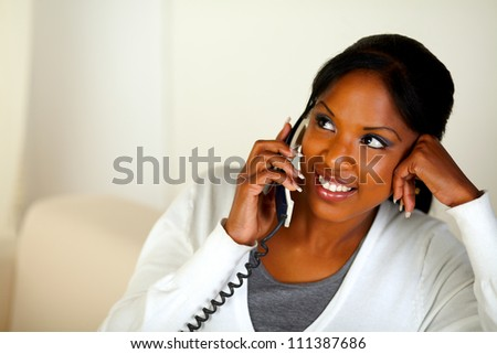 Portrait of an afro-American girl looking to her right on phone. With copyspace
