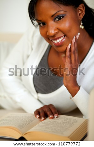 Portrait of an afro-American lady smiling and reading a book while lying on couch at home indoor - stock photo