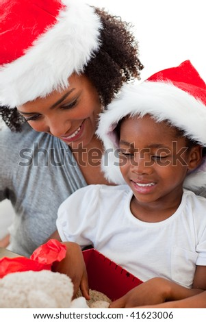 Portrait of an Afro-American mother and daughter opening a Christmas gift - stock photo