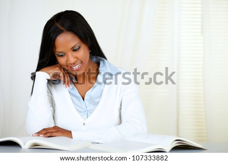 Portrait of an afro-american young black woman learning at soft colors composition - stock photo