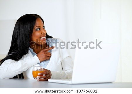 Portrait of an afro-american young woman drinking orange juice while is looking and pointing to her left in front a laptop at home indoor - stock photo