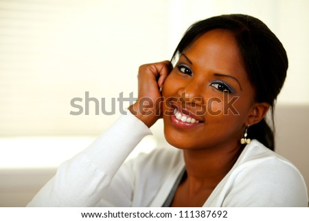 Portrait of an afro-American young woman looking at you at home indoor. With copyspace