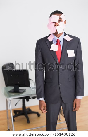 Portrait of an Afro businessman covered in blank notes at office - stock photo