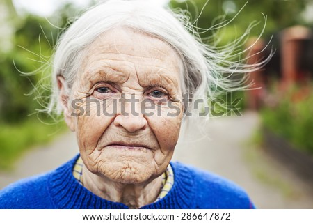 Portrait of an aged woman smiling outdoors - stock photo