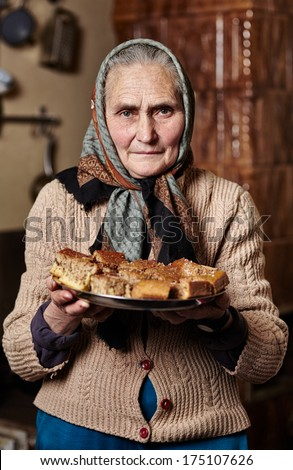 Portrait of an aged woman with kerchief offering a plate of homemade cookies - stock photo