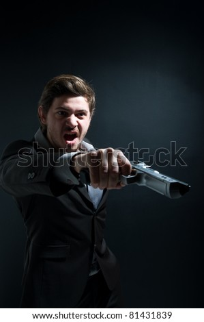 Portrait of an aggressive gangster holding a gun - stock photo