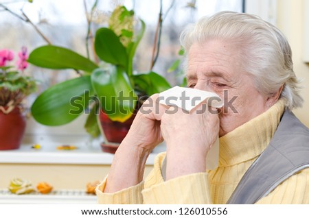 Portrait of an allergic mature female using a paper tissue - stock photo