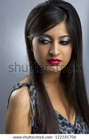 Portrait of an alluring lady not looking at the camera wearing a nice dress and make up - stock photo