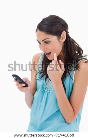 Portrait of an amazed woman reading a text message against a white background - stock photo
