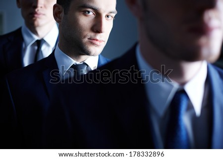 Portrait of an ambitious businessman through his colleagues on the foreground  - stock photo