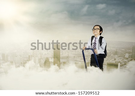 Portrait of an ambitious little businessman on a ladder stepping up - stock photo