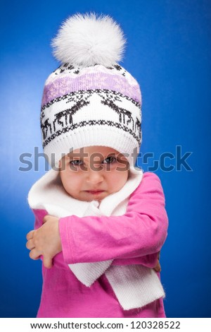 Portrait of an angry baby girl wearing a knit pink and white winter hat. - stock photo
