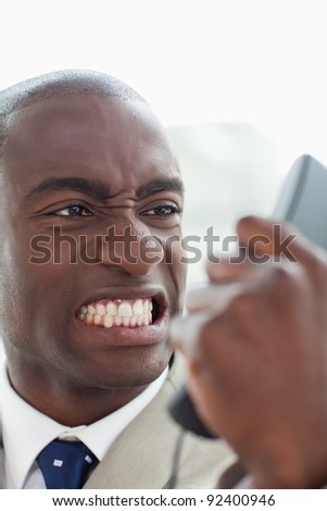 Portrait of an angry businessman looking at his phone handset in his office - stock photo