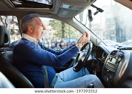 Portrait of an angry driver yelling in his car - stock photo