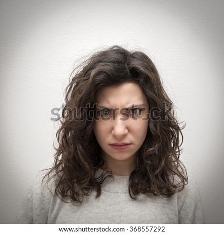 Portrait of an angry girl looking directly at camera - stock photo